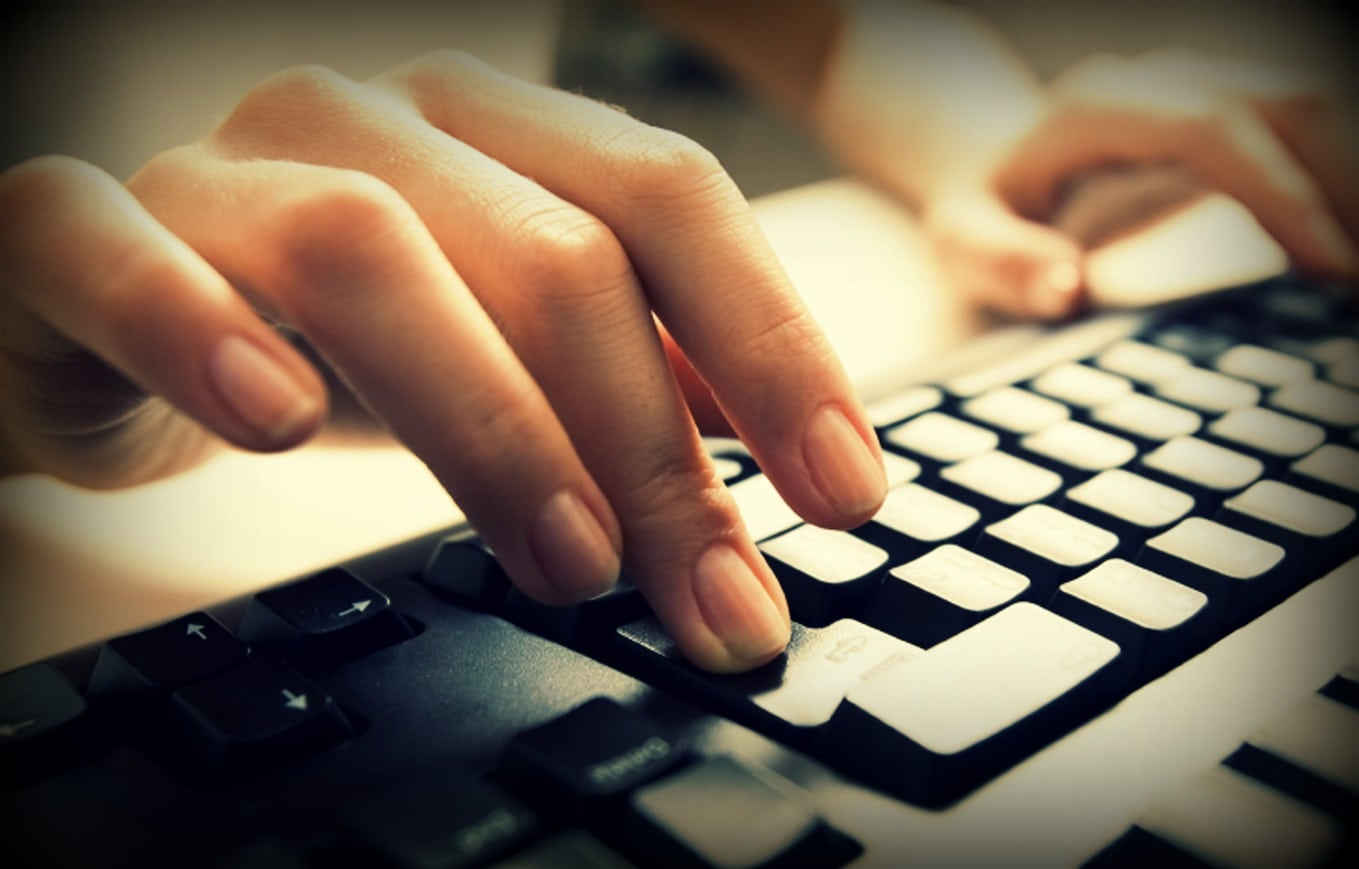 Close-up of female hands touching buttons of black computer keyboard