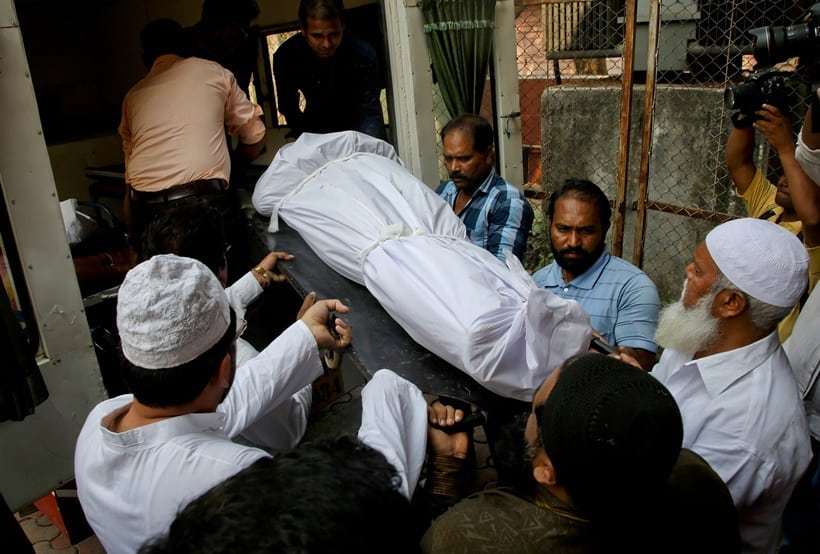 People carry the body of Indian man Hasnain Warekar, after autopsy from a hospital in Thane, outskirts of Mumbai, India, Sunday, Feb. 28, 2016. Warekar, 35 fatally stabbed 14 members of his family, including seven children, early Sunday before hanging himself, police said. (AP Photo/Rajanish Kakade)