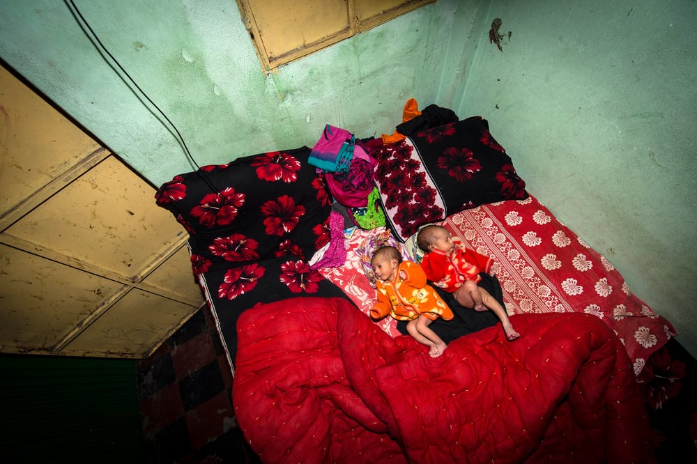 Five-day old twins lie on a bed. They do not yet have a name. Jhinik, 20 years old, is the sex worker who gave birth to them. © Sandra Hoyn. Finalist, LensCulture Portrait Awards 2016