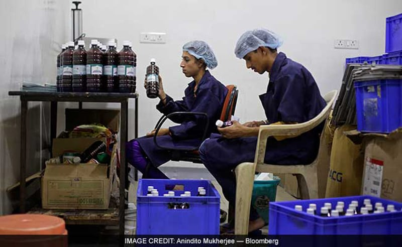 Workers label bottles of Swaarnim Natuscience Brantone+ cow urine syrup at the factory (Image Credit Anindya Upadhyay, Bloomberg)