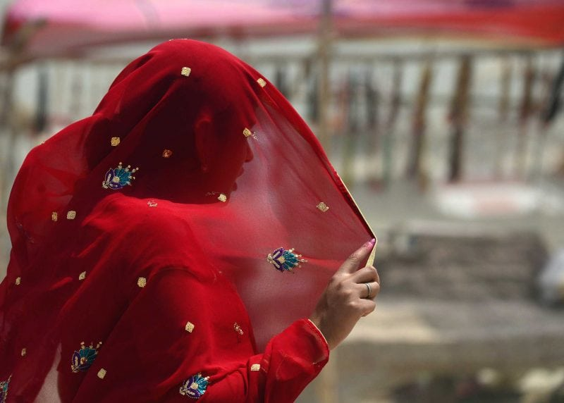 An Indian woman covers her face as she heads into a dust storm Getty Images
